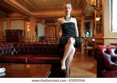 beautiful woman seated in a luxury interior - stock photo