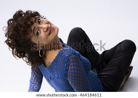 Beautiful woman, seated on the floor, looking for the camera and smiling.