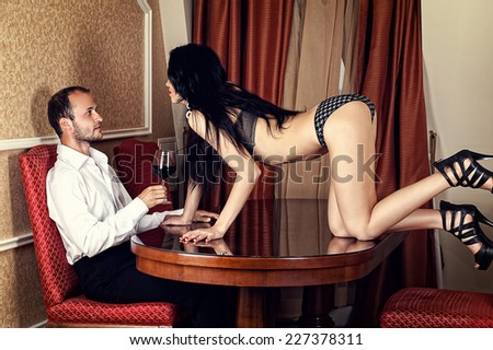beautiful woman seduces a man with a glass of wine - stock photo