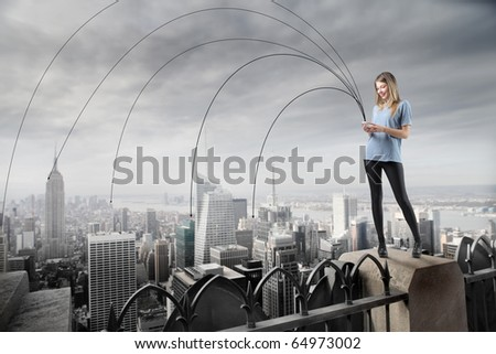 Beautiful woman sending sms to the whole city - stock photo
