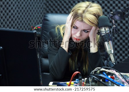 Beautiful Woman Serious And Moody While Working As DJ Radio Live Show In Studio - stock photo