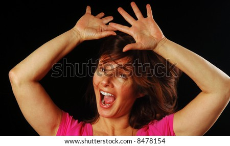 Beautiful woman shaking her head and holding hands up in a moment of wild abandon - stock photo