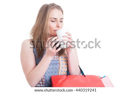 Beautiful woman shopper enjoying the smell of a fresh coffee and relaxing at shopping isolated on white with advertising area