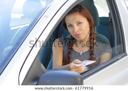 Beautiful woman show her driver's  licence in car. More images of this models you can find in my portfolio - stock photo