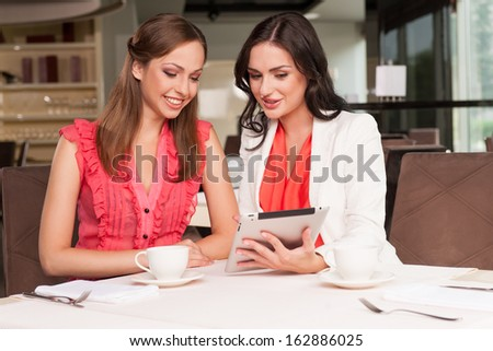 Beautiful woman showing her friend photos on tablet. Sharing memories from the trip or event  - stock photo