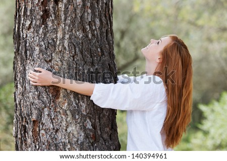 Beautiful woman showing her love of nature standing with her arms around the trunk of a tree looking up into the canopy with a lovely smile - stock photo