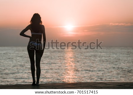 Beautiful woman silhouette over ocean sunrise background