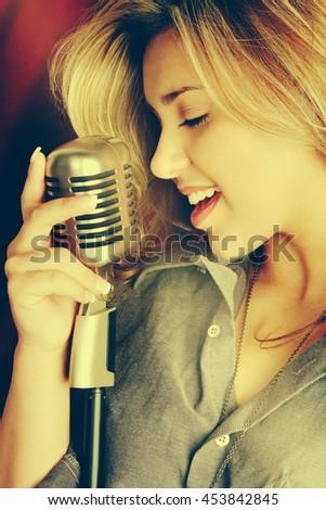 Beautiful woman singing into microphone - stock photo