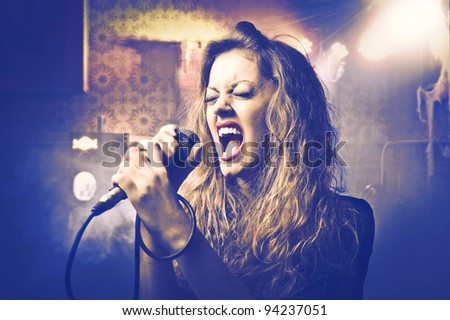 Beautiful woman singing into the microphone - stock photo
