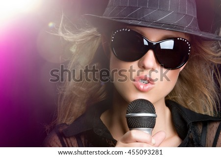 Beautiful woman singing karaoke in spotlight - stock photo
