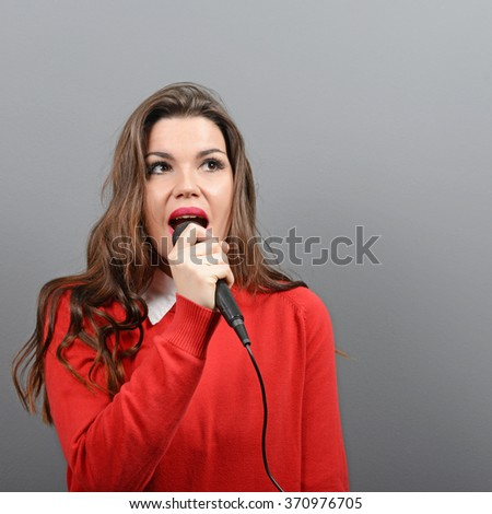 Beautiful woman singing with the microphone against gray background