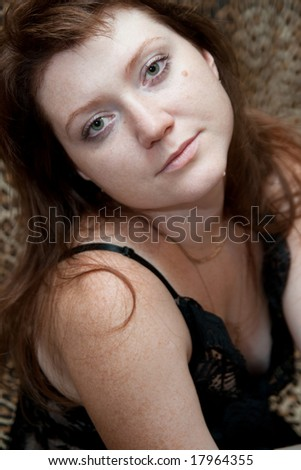 beautiful woman sit on sofa and look to camera