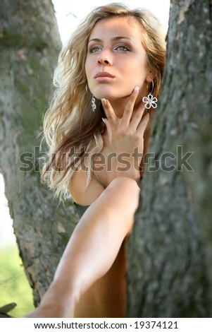 Beautiful woman sit on the tree.