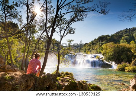 Beautiful woman sits at the waterfall in Krka national park, Croatia - stock photo