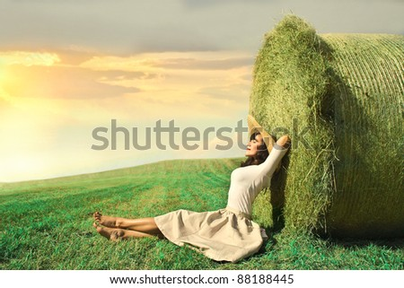Beautiful woman sitting against a haycock - stock photo