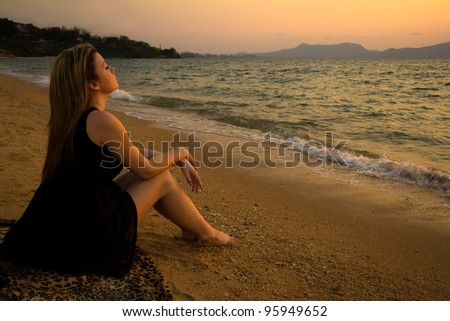 Beautiful woman sitting and relaxing on the beach at sunset - stock photo