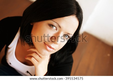 Beautiful woman sitting and  smiling indoors - stock photo
