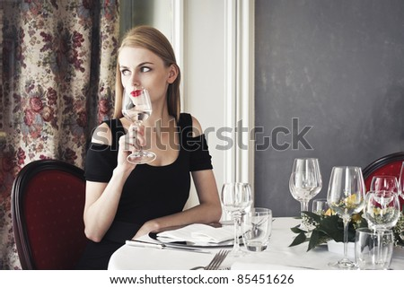 Beautiful woman sitting at a restaurant table and having a glass of water - stock photo