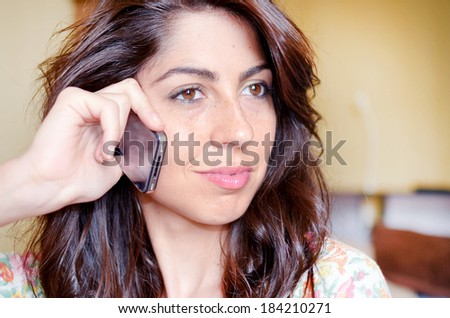beautiful  woman sitting at home and talking on phone - stock photo