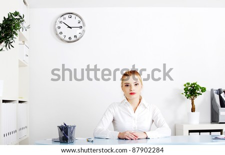 Beautiful woman sitting behind the desk in her office. - stock photo