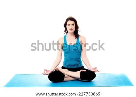 Beautiful woman sitting cross-legged and doing yoga - stock photo