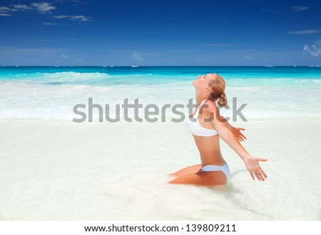 Beautiful woman sitting down on clean white sandy beach, enjoying sunny day, luxury tropical resort, summer vacation concept  - stock photo