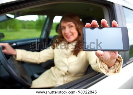 Beautiful woman sitting in a car and showing her smartphone out the window - stock photo
