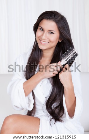 Beautiful woman sitting in a fresh white robe brushing her long straight brunette hair - stock photo