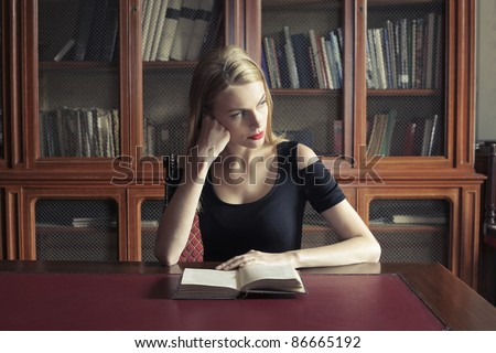 Beautiful woman sitting in a library and reading a book - stock photo