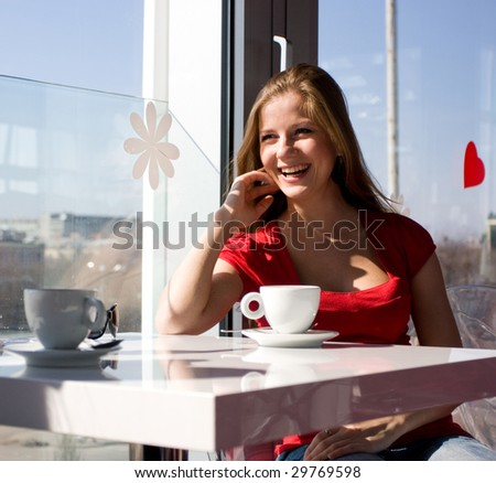beautiful woman sitting in cafe with cup of coffee - stock photo
