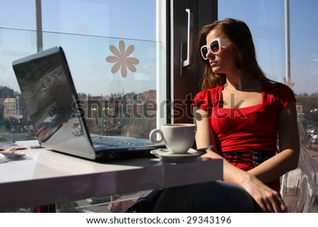 beautiful woman sitting in cafe with laptop - stock photo