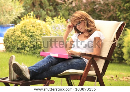 Beautiful woman sitting in garden and working at home. - stock photo