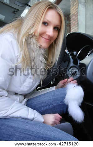 beautiful woman sitting in her car - stock photo