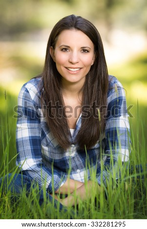 Beautiful woman sitting in long grass - stock photo