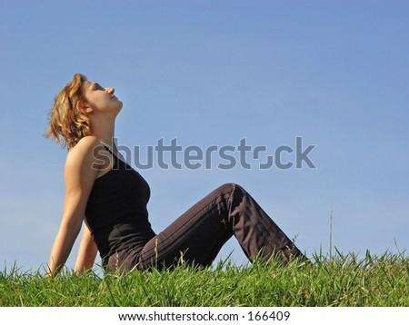 Beautiful woman sitting in the grass - stock photo