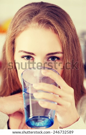 Beautiful woman sitting in the kitchen and drinking water. - stock photo