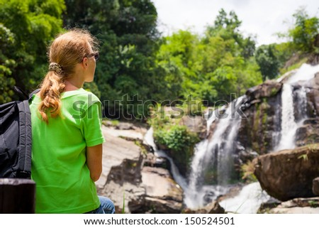 Beautiful  woman sitting near the waterfall enjoying the sun