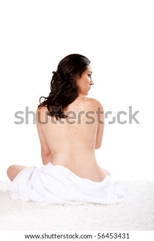 Beautiful woman sitting nude on soft surface with a towel around her bottom showing bare back with freckles, isolated. - stock photo