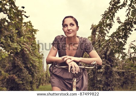Beautiful woman sitting on a bicycle - stock photo