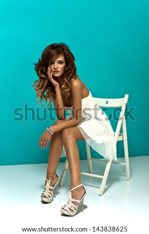 Beautiful woman sitting on a chair - stock photo