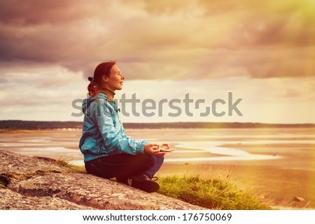 Beautiful woman sitting on a cliff over the sea and meditating