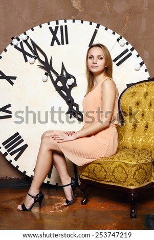 Beautiful woman sitting on a luxury armchair. Large retro vintage watches - stock photo
