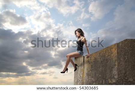 Beautiful woman sitting on a rock - stock photo