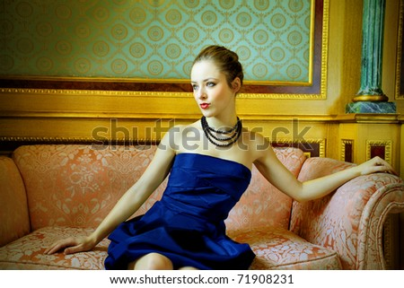 Beautiful woman sitting on a sofa in a luxury hotel - stock photo