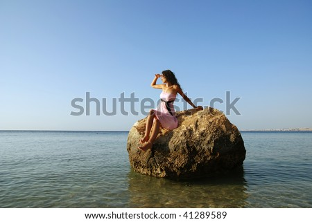 Beautiful woman sitting on a stone in the middle of the sea and looking far away
