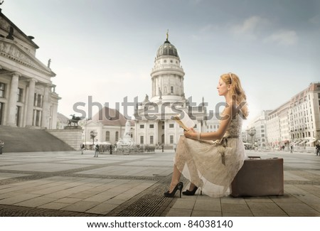 Beautiful woman sitting on a suitcase and reading a book with monument in the background