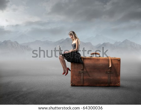 Beautiful woman sitting on a suitcase and using a laptop - stock photo