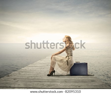 Beautiful woman sitting on a suitcase on a pier