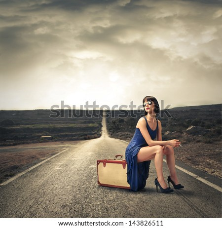beautiful woman sitting on a vintage suitcase on a desert road - stock photo