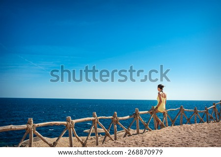 beautiful woman sitting on a wooden fence and looking at the sea. - stock photo